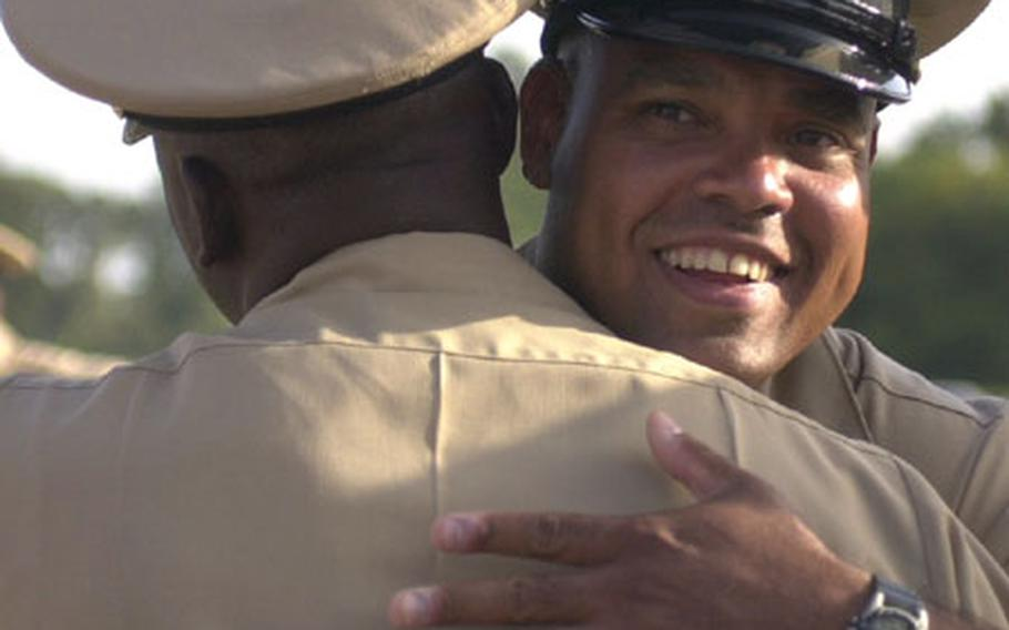"""Chief Petty Officer Angel Rivera hugs another chief after a pinning ceremony Wednesday at Naval Station Rota, Spain. The ceremony for 13 sailors tapped for the chief petty officer rank had been postponed as the result of """"inappropriate actions"""" at an initiation function on base Sept. 9."""