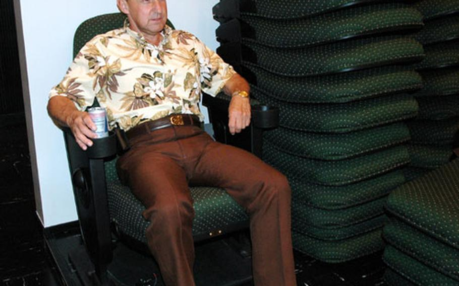 Frank DeSilva, public affairs specialist for Sasebo Naval Base's Morale, Welfare and Recreation department, tries out one of the new theater chairs being installed at the Showboat Theater. The 319 hunter green chairs are wider, better cushioned and equipped with drink holders.