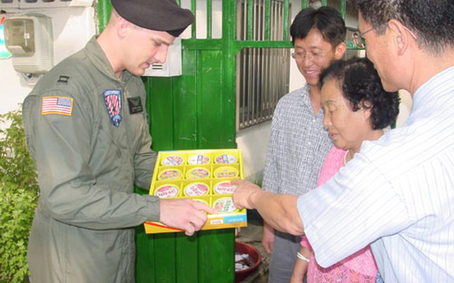 Capt. Matthew J. Bowman, commander of the Walker Army Heliport in Taegu, South Korea, explains the content of a Chusok gift set given to local residents living adjacent to the heliport Friday. The Army's Area IV Support Activity has given out gift sets to local residents for seven years. Chusok is one of Korea's major annual holidays and is similar to Thanksgiving in the United States.
