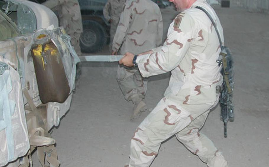 """Sgt. First Class Brian Hester, from Mount Sterling, N.Y, Company B's platoon sergeant also known as """"Ammo Can"""" by his men, tightens a strap on an armored Humvee before a Wednesday night's standard 12-hour mission."""