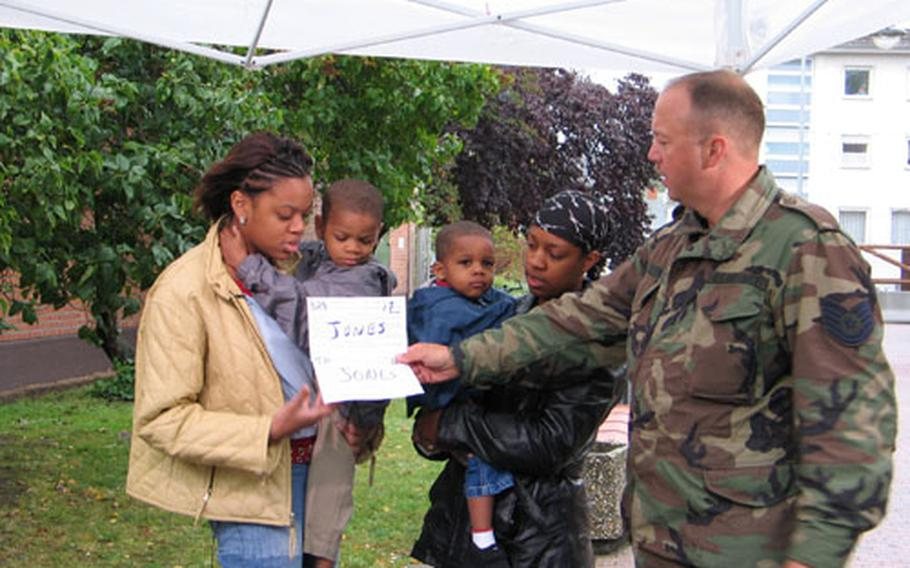 Air Force Tech Sgt. Eric Schwab assists Bamberg family members, left to right, Tamara, J'Don, Jamicka and Jamal Jones, of the 1st Battalion, 6th Field Artillery, in making holiday greetings to Savanna, Ill., and Rochester, N.Y. The Hometown News crew, based in Texas, recorded about 110 greetings at Bamberg's Warner Barracks last week. The Hometown News crews annually record greetings throughout Europe and Asia to bring holiday cheer from military families to the United States. Greetings are expected to air after Dec. 10.