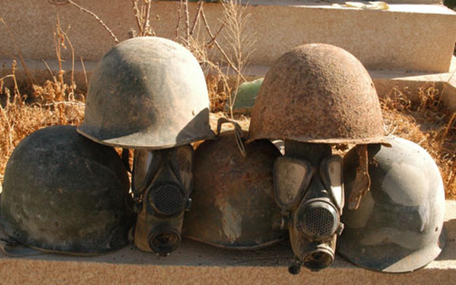 Iraqi helmets, gas masks and uniforms litter the grounds of Camp Habbaniyah, Iraq.