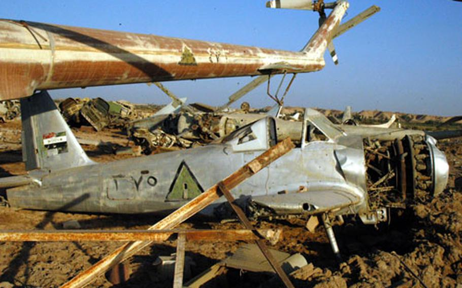 The aircraft graveyard at Camp Habbaniyah, Iraq, has all sorts of machines, including this single-engine prop plane flanked by a pair of helicopters.