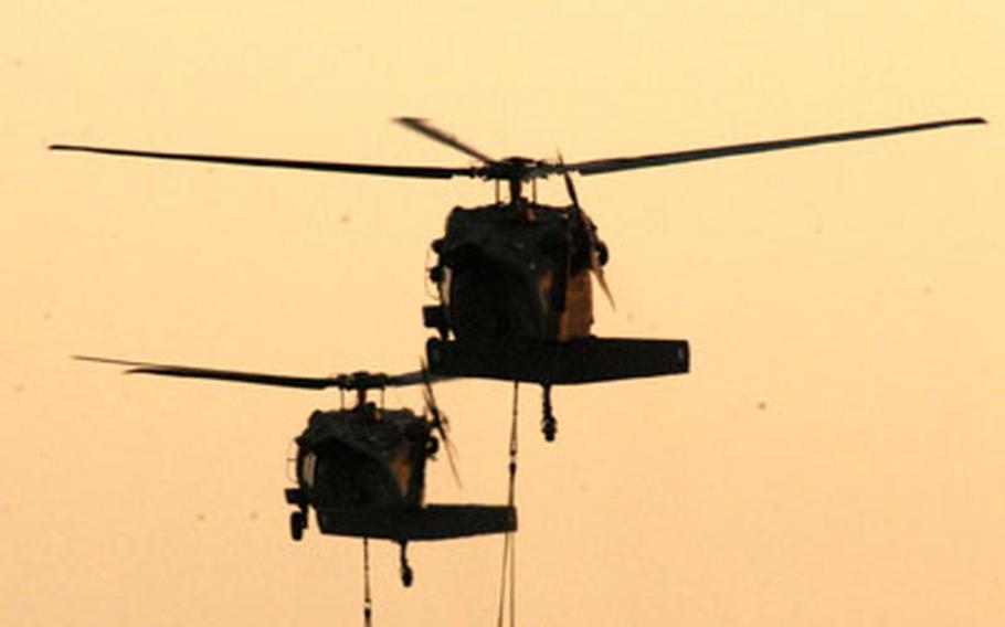 With air assault troops deployed to Iraq, helicopters carry concrete blocks to simulate Humvees and equipment for an infantry company.