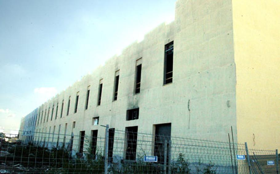 Damage to the outside of the exchange and commissary building under construction at the Naples Gricignano support site is limited to smoke streaks coming from openings in the cement walls. The fire was contained in the area, which was to be the building's cold storage facility.