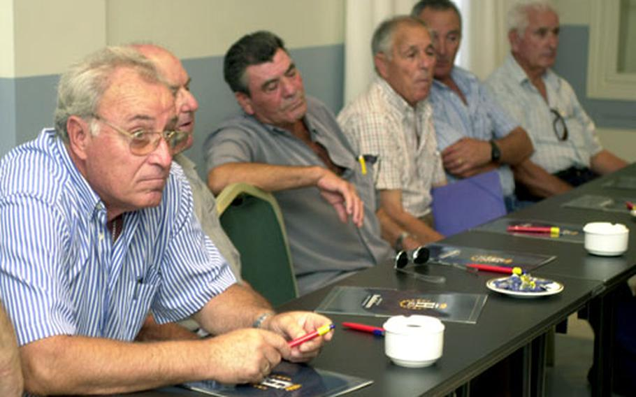 Retired U.S. Navy ship workers who were exposed to asbestos during the 1950s, '60s and '70s listen to attorney Mitchell Cohen at Hotel Playa de la Luz in Rota, Spain, on Tuesday.
