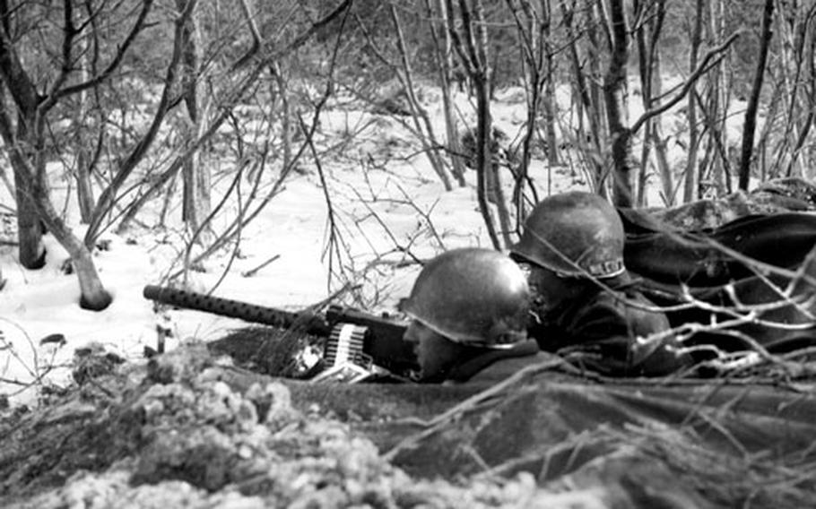 Two U.S. soldiers, dug into the snow and dirt east of Bastogne, Belgium, man .30-caliber light machine guns as they keep an eye out for German troops.