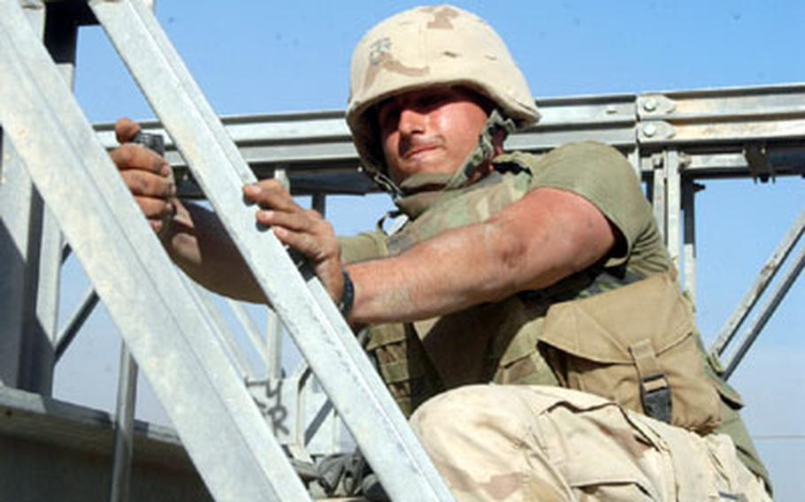 Marine Lance Cpl. Jesse Lester of Bridge Company A, 8th Engineer Support Battalion grimaces as he tightens a bolt on a bridge being built across the Tigris River.
