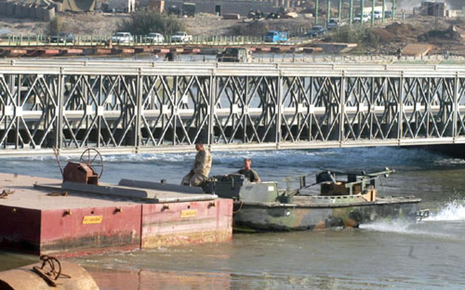 Members of the Marines' Bridge Company A use bridge erection boats to retrieve a span of a completed bridge that had broken free and was floating down the Tigris River. When all spans have been built, the bridge will be put in place to allow better flow of convoys across the river.