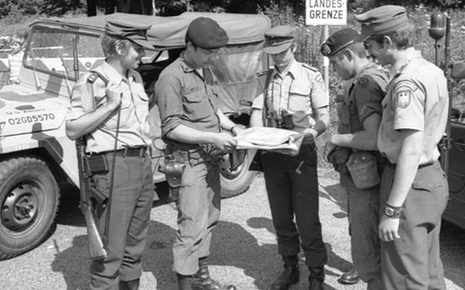 West German and U.S. troops at Camp Gates. In the background is a sign warning of the  (national border) with Czechoslovakia.