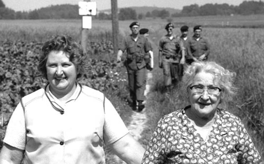 Soldiers on a routine patrol at the border between West Germany and Czechoslovakia share the path with a pair of local residents out for a stroll.