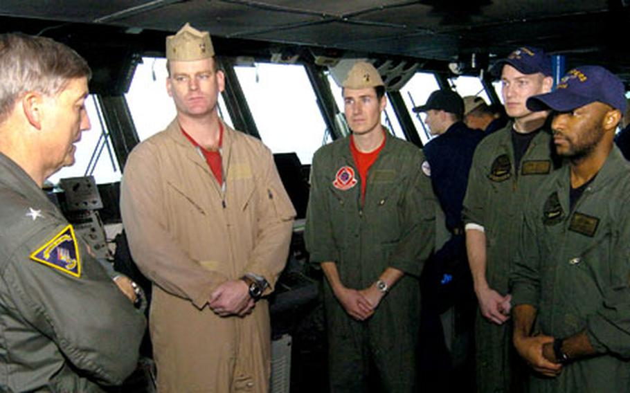 Rear Adm. James D. Kelly, far left, commander of Carrier Strike Group 5, congratulates aviation warfare systems operators Petty Officers 2nd Class Bennie Romiti, second from right, and Jerard Cook, far right, on Sunday for their rescue of Lt. Cmdr. Markus Gudmundsson and Lt. j.g. Jon Vanbragt of Strike Fighter Squadron 102 Saturday night.