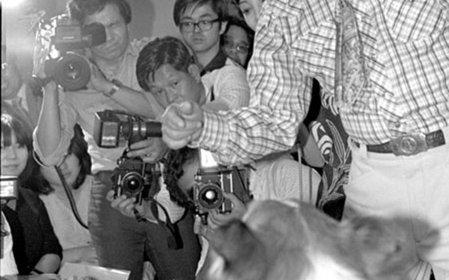 Lassie and trainer Rudd Weatherwax meet the press in Tokyo in June, 1979.