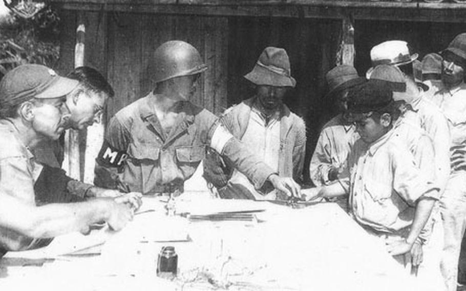 """Teruto """"Terry"""" Tsubota, center, wearing MP armband, registers Okinawa refugees during the Battle of Okinawa, which started 60 years ago."""