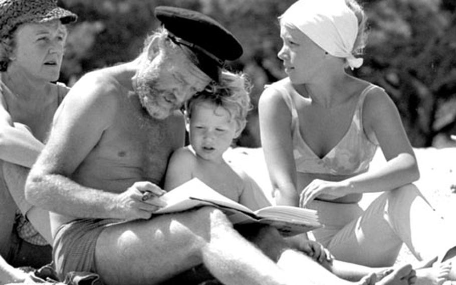 During a break in the filming, storytime on the beach for John Mills and his family.