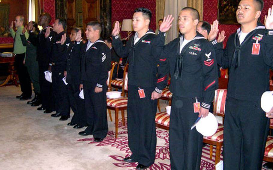Seventeen military members raise their right hands and read the oath of allegiance to the United States during a naturalization ceremony Thursday. The ceremony, held at the U.S. Embassy in Rome, was the first large ceremony held in Italy for military members.