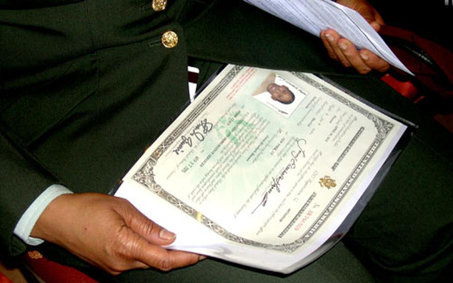 Spc. Jenny Elisabeth Haynes of the Southern European Task Force in Vicenza, Italy, holds her naturalization certificate after a naturalization ceremony. Haynes had been a citizen of the Netherlands.