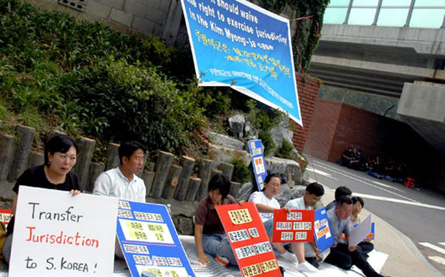 A small group of protesters sits in front of Gate 10 at Yongsan Garrison.