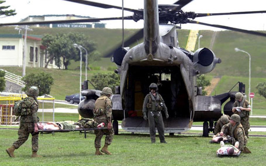 """Navy corpsmen assigned to the 31st Marine Expeditionary Unit's MEU Service Support Group 31 carry a mock patient to the back of a waiting CH-53 helicopter during a medical drill on Camp Kinser, Okinawa, on Monday. The corpsmen are part of a """"Nightingale Team."""""""