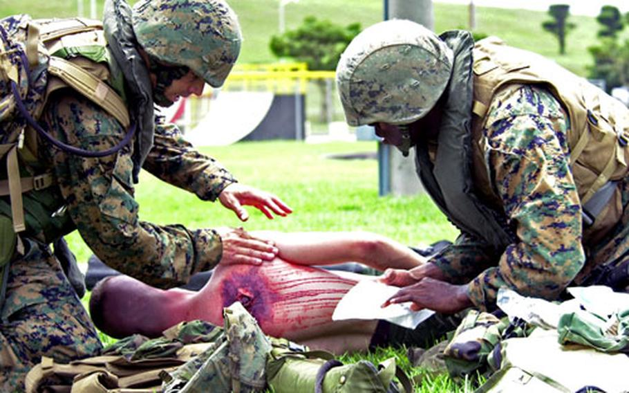 Two Navy corpsmen tend to a mock gunshot victim during the medical drill.