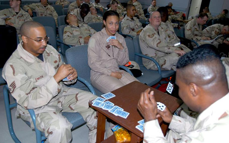 Some of the 300 Pacific Air Forces airmen waiting to deploy to the Middle East whittle away the time Wednesday at the passenger terminal at Misawa Air Base, Japan, with a game of cards.