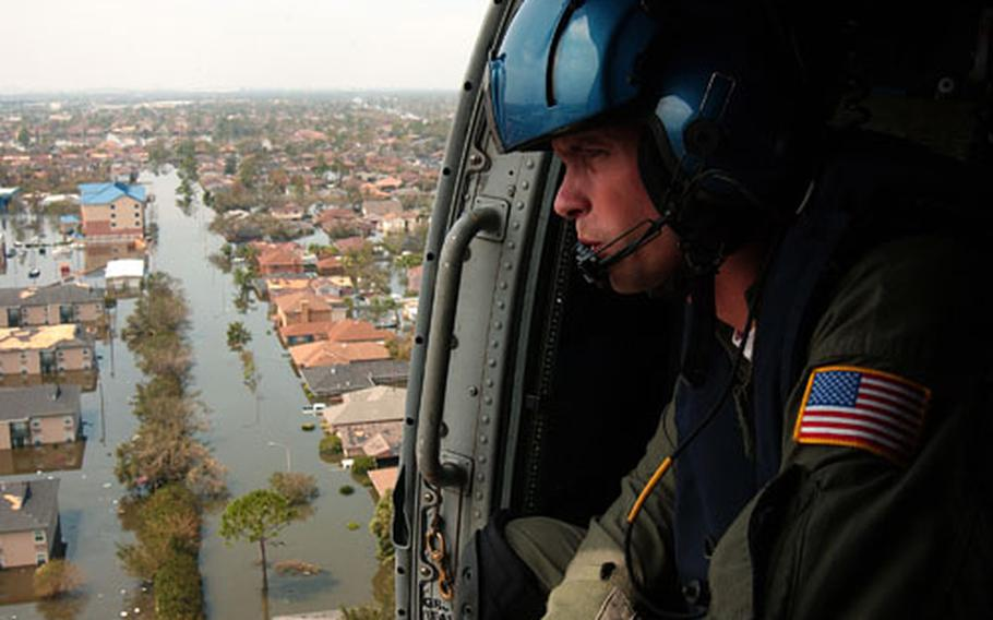 Petty Officer 2nd Class Shawn Beaty, 29, of Long Island, N.Y., looks for survivors Tuesday in the wake of Hurricane Katrina from the door of a rescue helicopter over New Orleans.