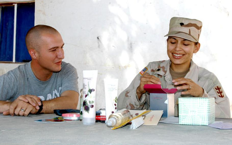 Spc. Sally Dominique opens a birthday present from her husband, Spc. Seth Dominique, in Mosul, Iraq. Their unit, the 94th Engineer Combat Battalion (Heavy), prohibits soldiers from engaging in any type of sexual activity while they are deployed to Iraq.