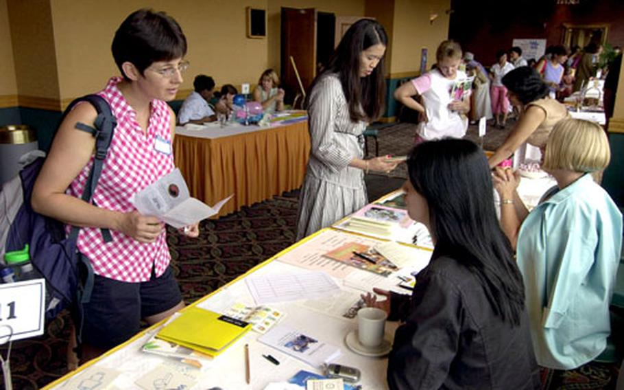 Lynne Vincenzo, left, talks to Park Seung-hee about the American Women's Club of Korea during an American Forces Spouses Club membership drive Thursday at Yongsan Garrison, South Korea.