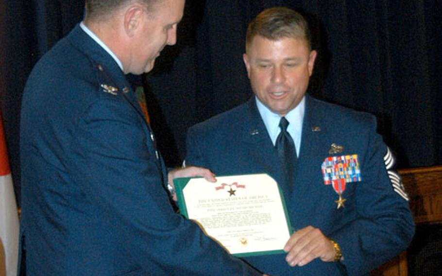 Col. Scott Goodwin, left, 374th Airlift Wing commander, presents the Bronze Star Medal to Chief Master Sgt. Carl Hunsinger during a ceremony Wednesday at Yokota Air Base, Japan.