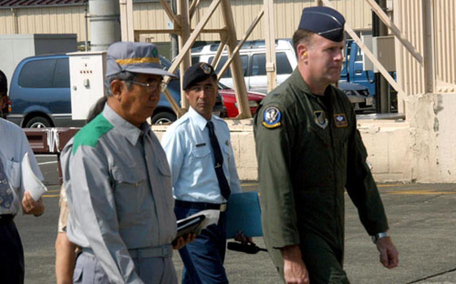 Tokyo Metropolitan Gov. Shintaro Ishihara, left, and Col. Scott Goodwin, the 374th Airlift Wing commander, observe Thursday's earthquake drill on Yokota Air Base's flight line.