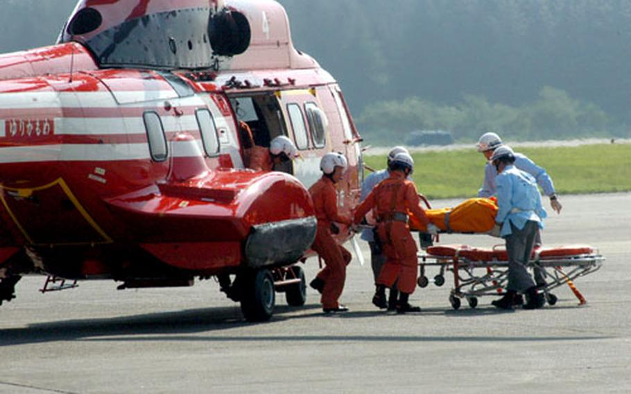 """Japanese rescue personnel remove an """"injured"""" patient from a Tokyo Fire Department helicopter during Thursday's earthquake disaster-prevention drill."""