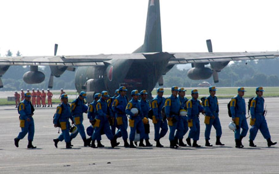 Tokyo Metropolitan Police Department members walk past a Japan Air Self-Defense Force C-130 during Thursday's drill.