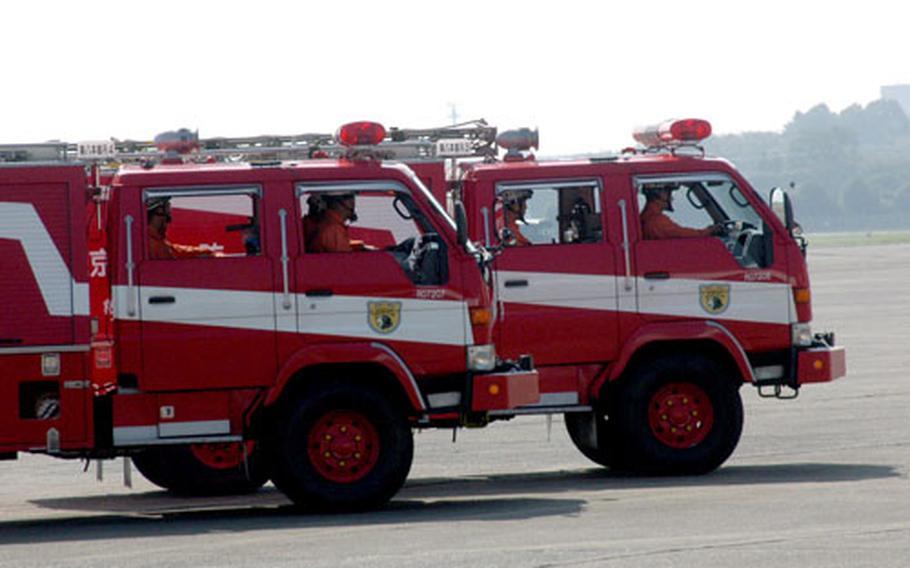 Tokyo Fire Department members arrive in rescue trucks.