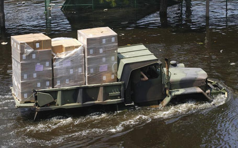 A National Guard multi-purpose utility truck fords the floodwaters left by Hurricane Katrina to bring supplies to the Super Dome in downtown New Orleans, La., Wednesday. Tens of thousands of displaced citizens sought shelter at the dome but are now being evacuated as floodwaters continue to rise throughout the area.