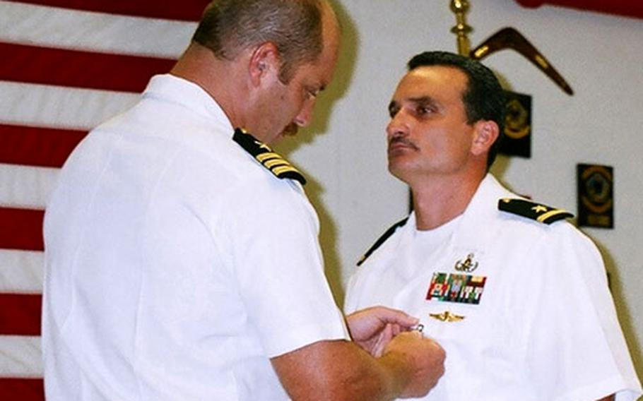 Ensign Troy Lawson, right, is presented with the Bronze Star Medal by Commander Vincent Martinez, commanding officer of Explosive Ordnance Disposal Mobile Unit 5.