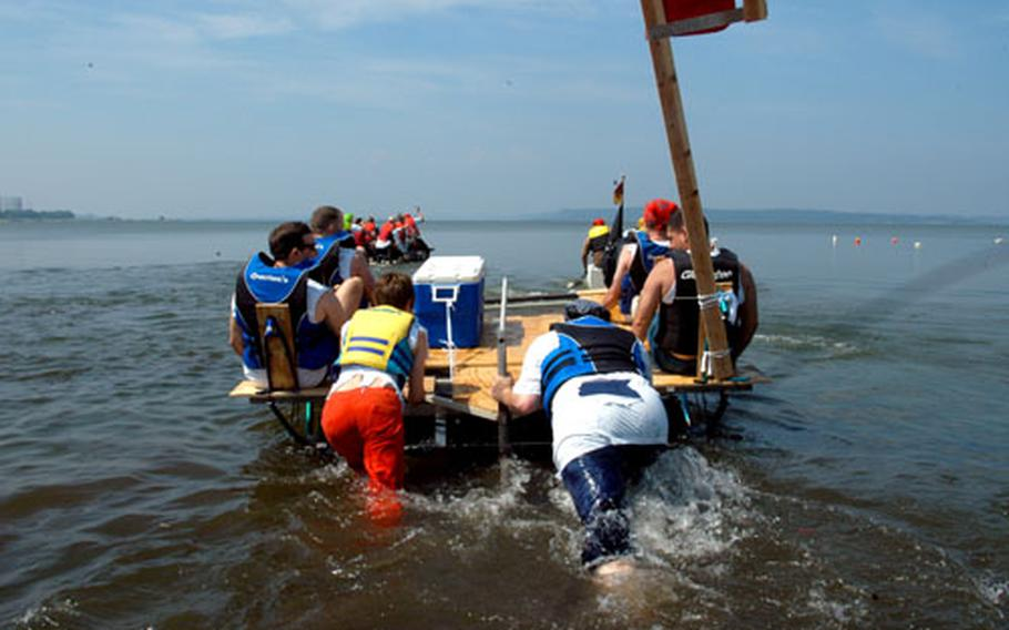 A team from the Aircraft Intermediate Maintenance Department try to get their bicycle-pedal-powered pontoon moving. Though voted most innovative, the metal-laden boat wasn't very buoyant.