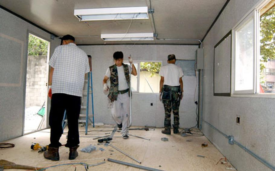 Electricians from the Area IV Support Activity's public works department work to convert a rusted old shipping container into a bright new classroom for the Taegu American School.