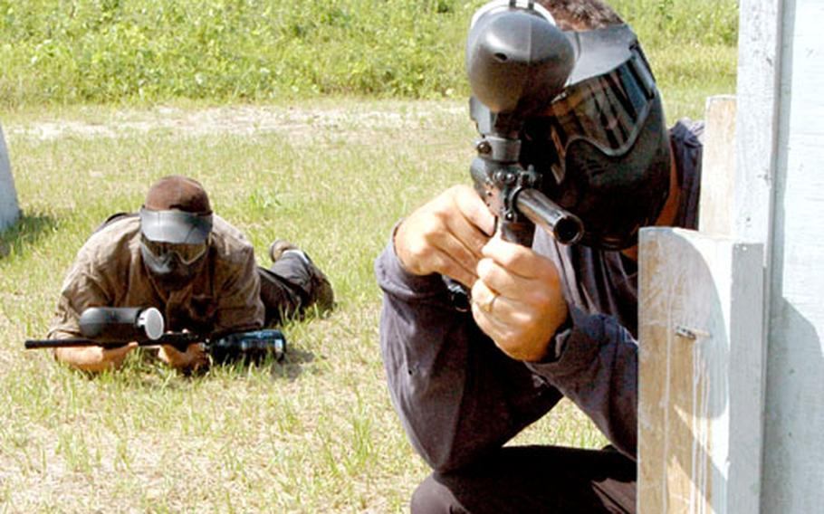 Trent Lake, right, and fellow Sailing and Outdoor Recreation Center employee Melvin Brook align themselves to move in on an opposing team at the new Sasebo paintball range.