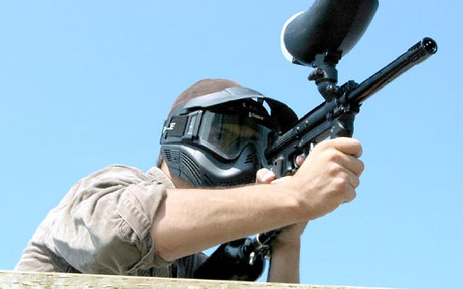 Sailing and Outdoor Recreation Center employee Johnny Devlin, having climbed on top of a barrier measuring about six feet high, aims his paintball marker.