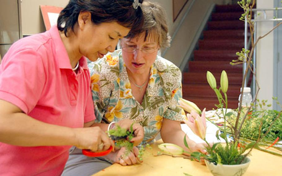 """Chung Hyun-suk, left, helps Kathy Hansen arrange flowers at the Arts and Crafts Center at Yongsan Garrison. The flower arranging class is Hansen's second at the center; last year she took a class working with Korean rice paper. """"I love this place,"""" Hansen said Wednesday."""