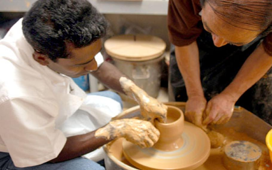 """David Joseph practices using the potter's wheel Wednesday afternoon at the Arts and Crafts center on Yongsan Garrison. Joseph, who also works on base, is taking a weekly pottery class from Han Yon-sok. """"Too hard, too hard,"""" Han repeated to his student, as Joseph practiced lengthening and shrinking the clay while trying to keep it perfectly round."""
