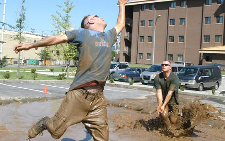 2nd ID soldiers Sgt. Jeff Howard, left, and Sgt. Thomas Gerrard play mud vollyball during the Camp Red Cloud block party on Labor Day.