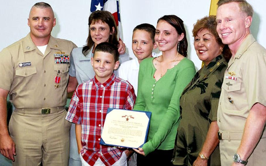 From left, Lt. Bryan Boudreaux; his wife Kristi Boudreaux; their children Kristopher, Bryan, Brittney; family friend Fran Faria and Rear Adm. Charles Leidig, commander of Naval Forces Marianas, stand with the Bronze Star Medal presented to Lt. Boudreaux, of the Military Sealift Command, at U.S. Naval Base Guam on Tuesday.