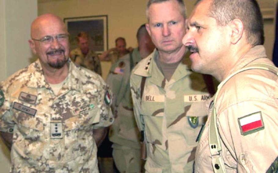 Italian Lt. Gen. Mauro Del Vecchio, commander of the International Security Assistance Force, left, and Bell talk with an unidentified soldier at right at the ISAF headquarters in Kabul, Afghanistan.