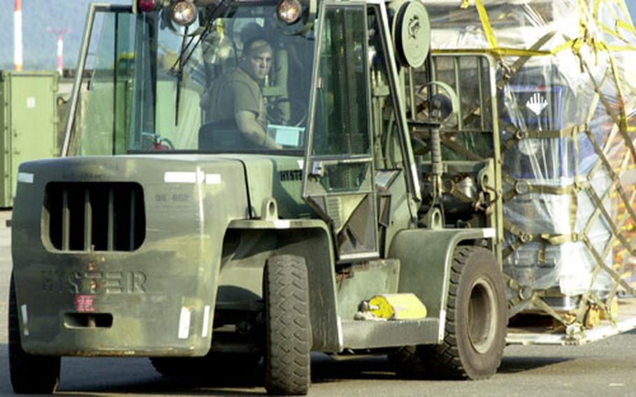 A U.S. airman in a forklift helps transport New Orleans-bound German pumping equipment at Ramstein Air Base, Germany, on Wednesday.