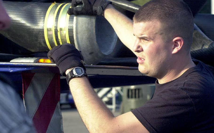 An American airman helps unload New Orleans-bound German pumping equipment from a truck at Ramstein Air Base.