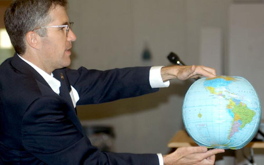 Mark Hofstadter, a scientist with the Jet Propulsion Laboratory at Pasadena, Calif., uses a model of Earth to represent the planet's orbit Thursday at Lakenheath Middle School at RAF Feltwell, England. He is a representative for a radio telescope program used by schools.