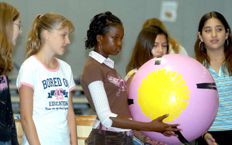 Pupils at Lakenheath Middle School pass around a beach ball Thursday to represent the long orbit of the planet Uranus around the sun.