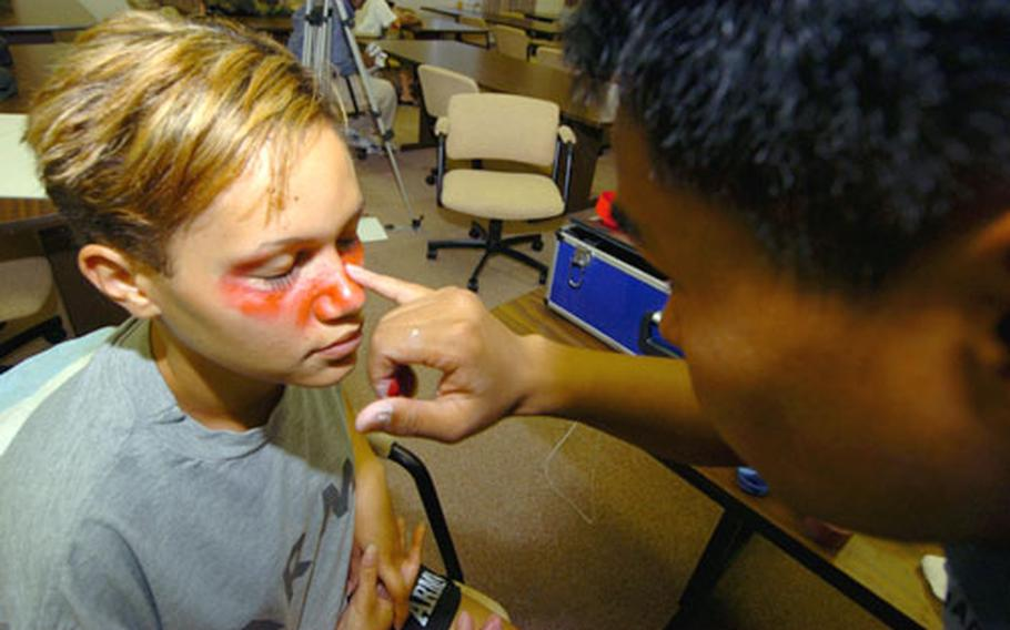 """Army Specialist Jaime Moore has """"blood"""" painted on her face by Hospital Corpsman Vicheath Phan. Both were taking part in a training exercise at Camp Zama, Japan."""
