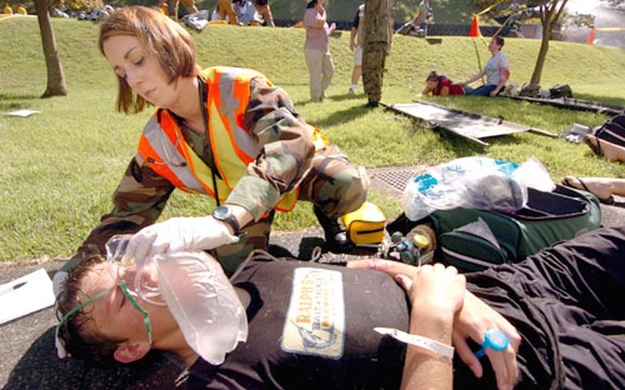 Army Specialist Arielle Mcallister puts an oxygen mask on ninth-grader Cambell Overly, who volenteered to play a victim in a training exercise at Camp Zama, Japan.